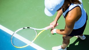 Image of woman preparing to serve a tennis ball