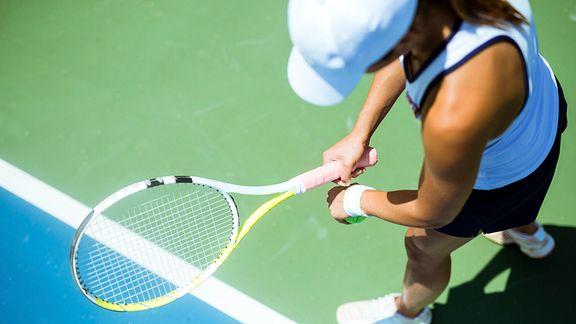 Woman preparing to serve on tennis court.