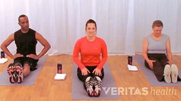 Two women and a man sitting on yoga mats in an exercise studio