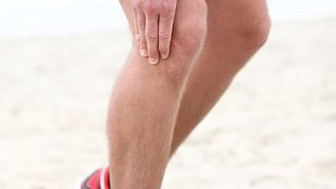 Runner on the beach grabbing knee in pain.