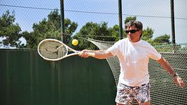 Man hitting a tennis ball on his forehand side.