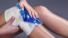 A person holding an icepack to their bandaged knee