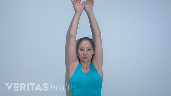 Woman against a wall doing a back burn stretch.