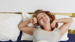 Woman lying in bed, stretching as she wakes up