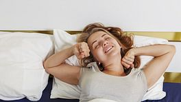 Woman laying down in her bed stretching as she wakes up
