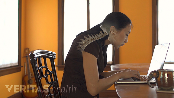 Video still of woman sitting, hunched over, at her laptop
