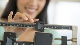 Woman on a scale adjusting her weight.