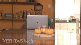 Man sitting at a table with his laptop