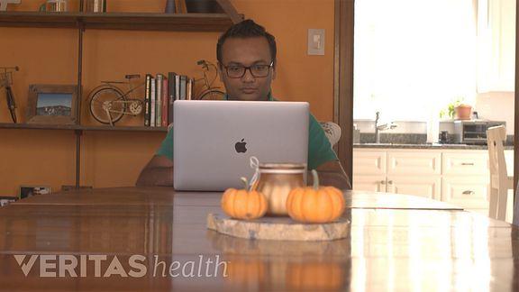 Man at a table looking at his laptop