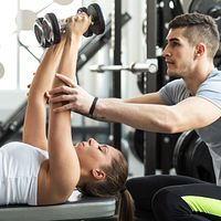 Athletic trainer working with a client lifting dumbbells.