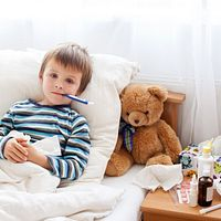 Child in bed with a thermometer.