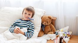 Child in bed with a thermometer in his mouth.