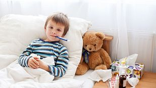 Boy in bed with a thermometer and teddy bear.