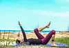 Image of woman doing the hook lying march exercise for sciatica pain relief outside on an yoga mat