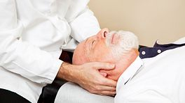 Chiropractor adjusting an older man's neck