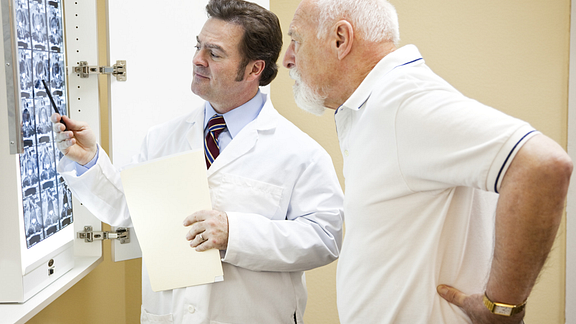 Image of a doctor and senior male patient with back pain reviewing CT scans