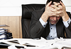 Image of a man with a headache sitting at a desk with scattered papers