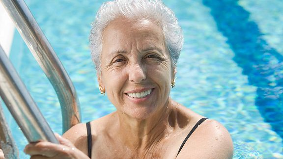 Older woman smiling and standing in a swimming pool