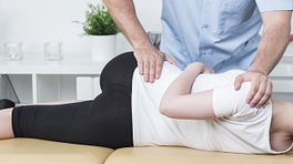 Practitioner manipulating a patient's lower back.