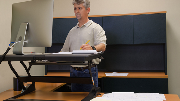 Image of man working at a standing desk