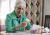 Image of a senior woman reading the information on her prescription pill bottles