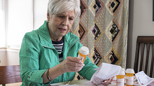 Image of a person sitting at a table reading the label on a prescription bottle