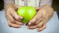 Arthritic hands holding an apple.