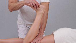 Chiropractor manipulating a patient's lower leg.