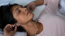 Woman putting in ear buds as she relaxes.