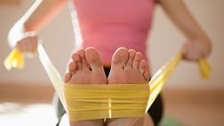 Woman flexing her feet using a resistance band.
