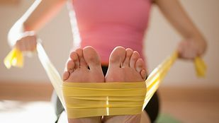 woman pulling a stretch band across her feet