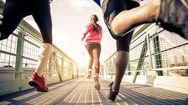 Group of three people running across a walking bridge.