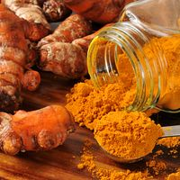 Spoonful of turmeric powder with turmeric roots in the background.