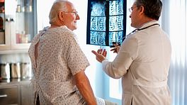 A doctor reviewing an xray of a patient spine with the patient