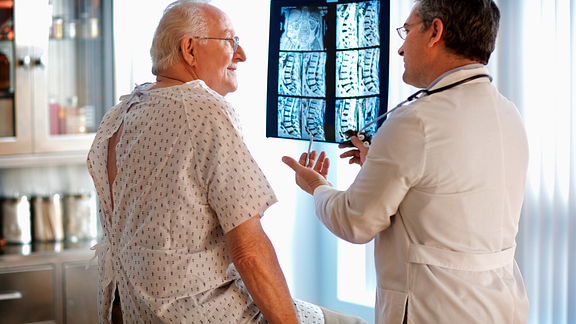 Image of doctor going over patient spinal MRI