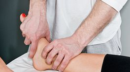 Physical therapist manipulating woman's ankle