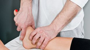 Examining a patient's ankle.
