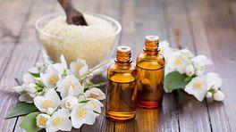 Bottles of essential oils alongside bath salts and flowers