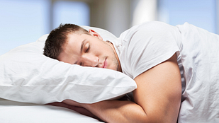 Image of young man sleeping in a bed with a pillow