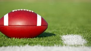 Football resting on the football field