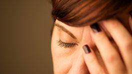 Woman grabbing her head with a headache.