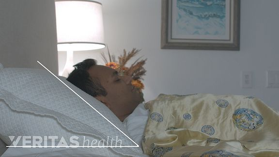 Man sleeping on his back with a thick pillow
