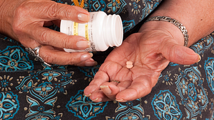 Image of senior woman emptying prescription pills into her hand