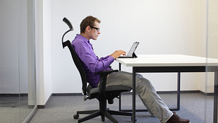 person sitting at a desk with incorrect posture