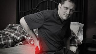 Man sitting on the side of his bed with radiating pain in his lower back