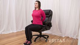 Woman performing reverse arch stretch in an office chair.