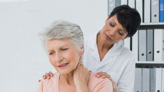 Senior woman with neck pain at the doctor