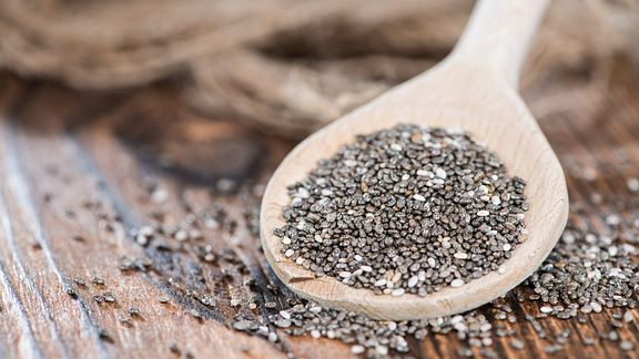 Wooden spoon full of chia seeds.
