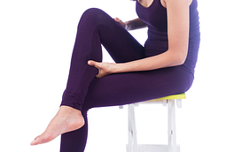 Image of a young woman sitting on the stool squeezing her calf