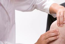 Closeup image of physical therapist examining a patient's knee